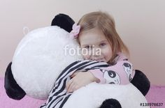 "Download the royalty-free photo ""Adorable little girl in nightgown playing with her soft toy panda. Child is happy with her bear. Tinted photo."" created by sebos at the lowest price on Fotolia.com. Browse our cheap image bank online to find the perfect stock photo for your marketing projects!"