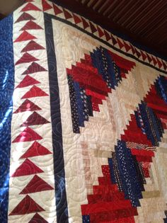 Close-up of uneven flying geese border on traditional Red, White, Blue log cabin quilt.