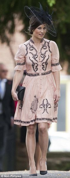 She accessorised with black heels, a matching clutch and a net and feather detailed hat