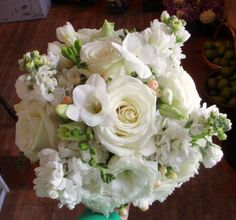 All White bouquet with Roses, Freshia, Stock, Lisianthus, and Hypericum Berries.