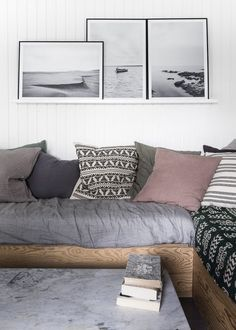 Foto Factory posters of nature in black and white colours hanging over a cozy couch in the livingroom.