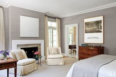 In the master bedroom of a Philadelphia-area house designed by Thomas Jayne, matching custom-made slipper chairs, covered in a Claremont fabric, flank the fireplace. The all-white canvas is by Robert Ryman, an early John Baldessari work hangs above a Dutch neoclassical chest, and the rug is from Patterson, Flynn & Martin.