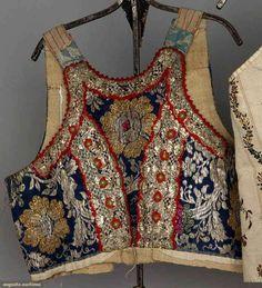 Eastern Europe, Five Women's Regional Garments : 1 Albanian red & white striped jacket ; 1 German quilted & printed vest ; 1 German cream silk & brocade vest ; 1 Slovakian metallic brocade vest ; 1 Slovakian embroidered blouse, 1850-1899