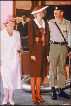 October 1985:  Diana visiting Puckapunyal, Australia.  She is wearing a Victor Edelstein dress in deep plum, very fitted w/ a wide belt and a deep neckline edged w/ a white collar. Her matching hat is by Frederick Fox.