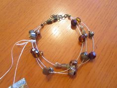 The bracelet is 3 thin gold tone wires that are held together with a gold plated clasp to fasten up and has small gold/brown glass beads going along them.   eBay!