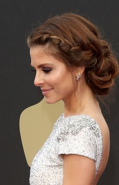 Recreate this braided updo by working mousse through your hair to boost waves and braiding French plaits that frame each side of the face. Stop braiding at the nape and secure each side with small rubber bands. Then, coil all of your hair in half-inch pieces and secure with bobby pins around the nape, creating an unstructured, round shape.