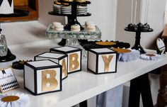 black white and gold modern baby shower dessert table