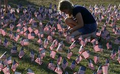 A girl plants some of the 3000 flags placed in memory of the lives lost in the September 11, 2001 attacks, at a park in Winnetka, Illinois