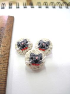 Cross-stitched buttons--tiny cats...with whiskers! By Pin Pals