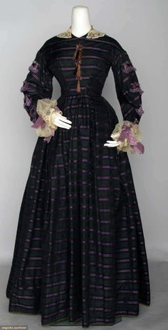 "Black & Purple Brocade Day Dress, 1860s. 1-piece black w/ purple stripes, fringed & scalloped lavender trim, skirt w/ box pleats, B 35"", W 25"", L 57"""