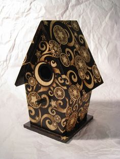 Many hours went into the creation of this one-of-a-kind wooden birdhouse, intricately decorated with wood burned celestial swirls and henna star