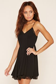 A textured woven dress featuring scalloped lace trim, a flared silhouette, adjustable spaghetti straps, a V-neckline, and an invisible zipper in back.