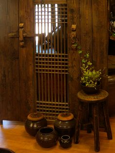 Korean traditional home decor idea.  Beautiful matching color of wood & pottery.