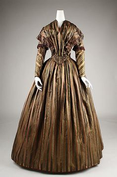 Striped silk taffeta dress with fly fringe trim, probably French, 1842. The dress buttons down the back with thread-covered buttons.