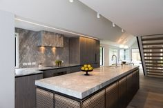 Lazer cut back lit island, paired with warm wood cabinetry ,  (splash back not right)