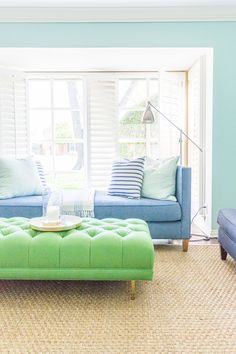 Anthropologie Mina cocktail ottoman in emerald linen - colorful living room - Crypton fabric-covered daybed in Daily Denim - sisal rug - transitional decor style - www.pencilshavingsstudio.com