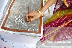Woman painting her doorstep with rice flour paste, making rangoli design Diwali Festival decorations, Udaipur, Rajasthan, India