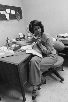 1975 An office worker takes a phone call. She wears a loose-fitting cardigan with a wide collar and wide, loose pants. Her shoes are unusually patterned. She wears a bracelet and ring, and her hair is lightly styled.