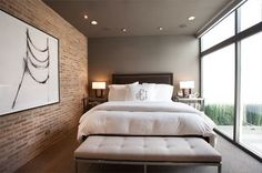 Warm, cozy, contemporary bedroom:  Brick wall, modern art, gray feature wall, floor-to-ceiling window wall.