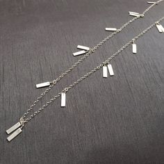 Silver Confetti Station Necklace; handcrafted with love, this minimalist style necklace has 16 handmade fine silver (.999%) rectangles wired wrapped around the long sterling silver chain. Total Length: 33.5, makes a perfect layering piece or worn alone. It is subtle, delicate, and sturdy. Connecting rings are all soldered. ($100) #minimaliststyle #modernjewelry #geometricjewelry