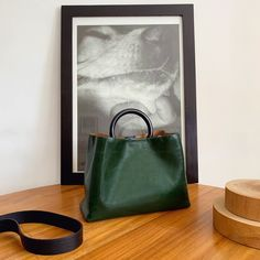Miller tote has a round top resin ring handle that you can clutch in hand or slip over your wrist. This large version has plenty of space for the essentials and has two centre pockets for your phone and cards close to hand. Attach the strap to carry it on the shoulder.