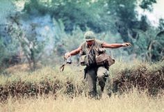 American soldier armed with an M79 grenade launcher crosses a field. Photographed by Eddie Adams.