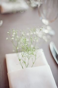 So sweet —a little sprig of baby's breath gently tucked into a folded napkin.