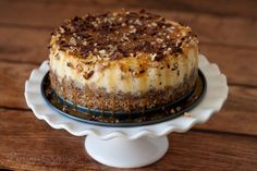 Rich, dense New York cheesecakepaired with a crumbly toffee pecan shortbread cookie crust, then decorated with caramel topping, chopped pecan, crushed toffee bits, and grated chocolate.