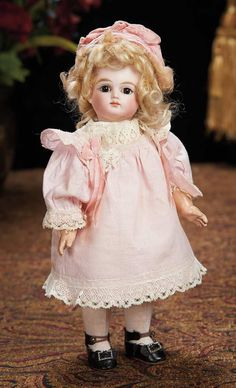 28 cm. Wonderful Petite French Bisque Bebe by Schmitt et Fils. Marks: Sch (in shield) 4 (head) T.D (in shield on bottom torso). Comments: Schmitt et Fils, circa 1880, the body marking is a mystery and it is uncertain if the body is original to this doll although certainly French, of the same era and appropriately sized.  5500/7500