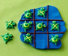 """This darling rendition of tic-tac-toe will have you and your little ones wondering why this classic game never revolved around this slow-moving reptile before now.                 Make It: Roll a large green ball and a small green ball from Crayola Model Magic or clay; press them together and flatten to make a turtle head and body. Next, roll a thin green snake-shape and cut four short pieces for legs. Use neon green clay to roll two tiny eyes; press them onto the body. Add a neon green """"X""""…"""