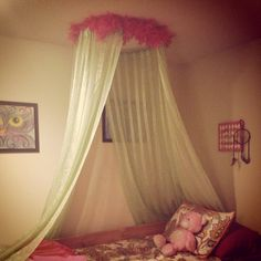 What do you get with an old hoopla-hoop, unused curtains and a feather boa? A canopy bed in about ten minutes!