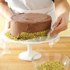 Adding lower edging of Nuts. For the nut edge, place strips of plastic wrap just under the edges of the frosted cake. Sprinkle chopped nuts on the wrap. Gently lift the wrap while pressing nuts into the frosting. Using a clean spatula to lift one side of the cake at a time, pull wrap out from underneath.