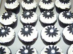 Black & White cupcakes - boxed individually & used as favours for guests at a 5oth birthday meal. Pure white buttercream, black gerberas & a touch of edible shimmer!