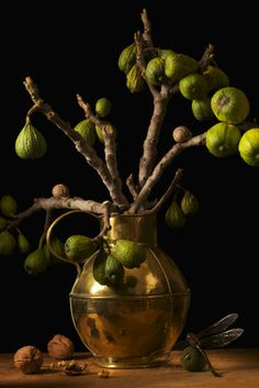Figs: Branches of green figs in a brass vase. Is that a dragonfly in the corner? Source: Paulette Tavormina