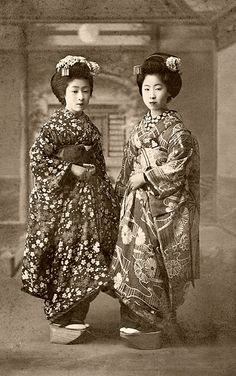 Cherry Blossoms and Chrysanthemums 1910s. Two Maiko (Apprentice Geisha) wearing Autumn ensembles. The girl on the left-hand side of the picture is wearing a classic combination of Sakura (cherry blossom) and Momiji (maple leaves), together with a Rangiku (spider chrysanthemum) Eri (inside collar), while the girl on the right-hand side of the picture is wearing Kiku (chrysanthemums) and Kikyou (Chinese bellflower).