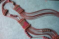 Farbkombination Grün, Lila und Braun. Makramee-Plättchen mit Metallornament fließend im gewachstem Garn verarbeitet.