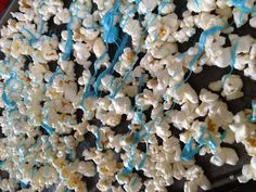 "Drizzle melted blue chocolate over popcorn for ""Ready to Pop"" baby shower theme favors"