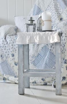 blue  and white quilt as chair cover and small stool as a table