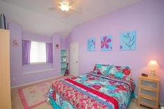 Fun and bright girls bedroom with purple walls and window curtains.