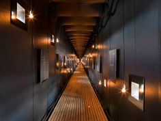 Steilneset Memorial / Peter Zumthor and Louise Bourgeois, Norway - Zumthor's pine scaffolding supports a suspended silk cocoon. Within the cocoon, visitors walk along a 400-foot long oak-floored corridor. A hanging light bulb floats behind each of the 91 windows, illuminating them in memory of the 91 individuals who were convicted of sorcery and burnt at the stake. Each window is accompanied by a plaque that reveals the story of each individual.
