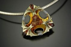 14k yellow and white gold pendant holding a scalloped trillian concave faceted citrine (by Richard Homer) accented with hessonite garnets, fancy colored sapphires and baguette cut diamonds.  One of the creations of Thomas Dailing Designs.