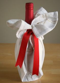 Cute way to cover a bottle of wine.  Use a tea towel and some ribbon.