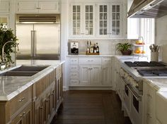ZsaZsa Bellagio: Dreamy East Hampton Kitchen, white kitchen cabinets, glass upper kitchen cabinet doors, oven hood, wood island, stained island, marble countertops