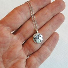 Unique, simple, and affordable.  The earth symbolizes all life. A wonderful gift for a graduate or loved one going on a journey.   This tiny earth charm necklace is perfect for everyday wear. Simply stylish and comfortable. Perfect for layering or on its own.  You may choose your length of sterling silver or stainless steel chain. The chain has a lobster clasp and is 1.5mm in thickness. Stainless steel is hypoallergenic and will not tarnish or cause irritation to sensitive skin. It is a…