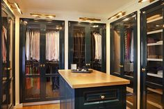 source: Bonesteel Trout Hall  Gorgeous walk-in closet with peacock blue glass-front closet doors, peacock blue closet island with butcher block top, brass picture lights and hardwood floors.