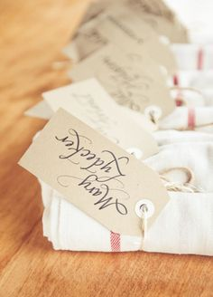 Escort card tags tied around napkins; guests take one and bring their napkin to their seat.