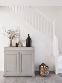 A gray chest under stairs styled with a vase of branched, a framed drawing, a black ceramic jar, and pieces of wood - Scandinavian Style - Home Decor Details