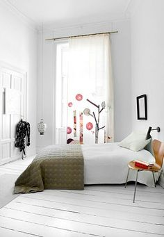 I like the little pop of colour the appliqued window panel gives to this white room