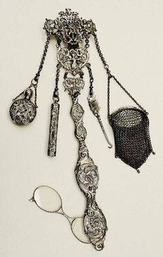 A chatelaine is a clasp with a series of dangling chains. These were worn on the belts of housekeepers in the 19th Century and held useful household items such as keys, seals, scissors, a watch or magnifying glasses. Though many chatelaines were purely utilitarian (i.e. Mrs. Hughes' chatelaine in Downton Abbey) some were beautifully crafted pieces of jewelry.