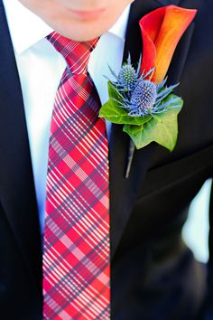 The groom gets a different boutonniere from the groomsmen. An orange calla lily looks great!